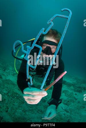 Un buzo bajo el agua recogida de basura de plástico en los fondos marinos, la celebración de una percha de madera desechados y un bolígrafo, buceo en la isla de Mabul, Sabah, Malasia.