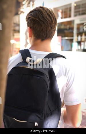 Vista trasera de corte limpio y vistiendo un adolescente masculino tshirt blanco con mochila en la espalda en la calle