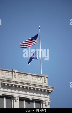Bandera Americana y ondear la bandera del estado de Indiana en la brisa en la cima de un edificio en el Monument Circle en Indianápolis, Indiana.