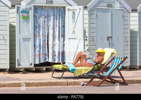 Bournemouth, Dorset, Reino Unido. 21 de julio de 2018. El clima del REINO UNIDO: caluroso y soleado en las playas de Bournemouth, como sunseekers, diríjase a la playa a tomar el sol en el comienzo de las vacaciones de verano. Mujer de más edad del sol la lectura de periódicos en sunlounger fuera de cabañas de playa. Crédito: Carolyn Jenkins/Alamy Live News Foto de stock