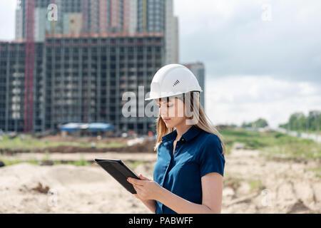 Ingeniero de la construcción femenina. Arquitecto con un equipo tablet PC en un sitio de construcción. Mujer joven busca, sitio de construcción lugar en segundo plano. Concepto de construcción