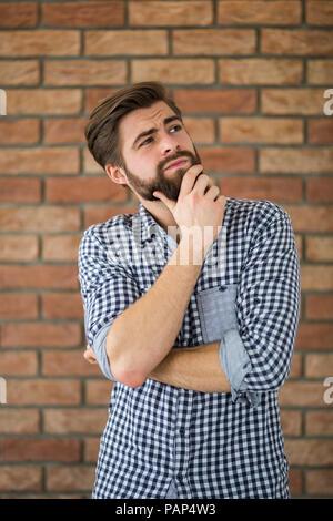 Retrato del joven barbudo delante de la pared de ladrillo pensando Foto de stock