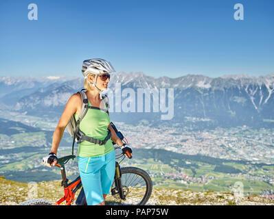 Austria, Tirol, Mujer Bicicleta de montaña en Patscherkofel, Innsbruck en segundo plano.
