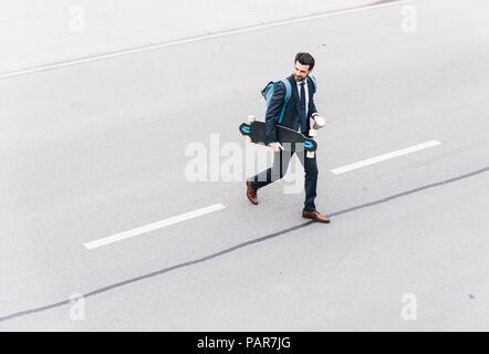 Empresario con café y comida para llevar en la calle monopatín Foto de stock