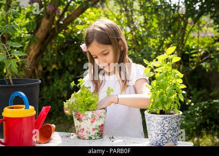 Retrato de niña macetas de perejil sobre la mesa en el jardín