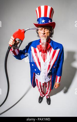 El Tío Sam de pie con una bomba de gas nozzel celebró en frente de él. Captura conceptual representando la adicción al petróleo americano / gas / petróleo.