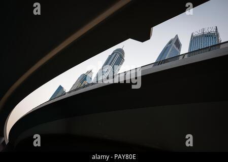 DUBAI, EMIRATOS ÁRABES UNIDOS - 15 de febrero de 2018: Dubai Marina con edificios más altos vistos a través de la brecha entre el puente las carreteras desde abajo, Emiratos Arabes Unidos Foto de stock