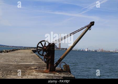 El Rusty cabrestante usado originalmente para transportar alimentos para para la Poolbeg guardafaros con las chimeneas de la antigua central eléctrica y el Puerto de Dublín Foto de stock