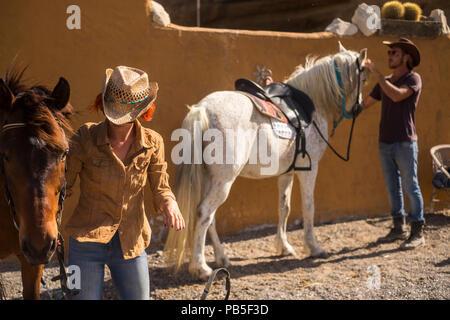 Pareja en campo preparan los caballos para ir viajando en el exterior y descubrir nuevas ntaural plces en excursión. Estilo de vida al aire libre para la felicidad y el pet ther Foto de stock