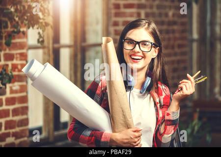 Lindo joven arquitecto hembra pelo largo anteojos con auriculares manteniendo copias heliográficas y sonriente cerca de la ventana en el loft oficina moderna