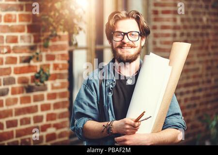 Attractiwe barbudo cabello oscuro arquitecto masculino lleva gafas celebración blueprints y sonriendo cerca de la ventana en el loft oficina moderna