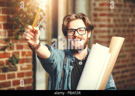 Attractiwe barbudo cabello oscuro arquitecto masculino lleva gafas celebración blueprints y lápices, él sonriendo cerca de la ventana en el loft oficina moderna