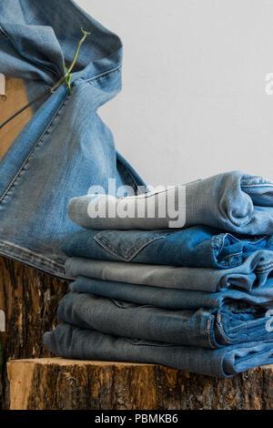 Pares de pantalones vaqueros colgados en un viejo tronco de madera, fondo blanco con espacio de copia