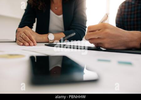 Cerrar centrados manos de colegas de negocios en una reunión discutiendo el trabajo. Empresaria en una reunión con un compañero de oficina.