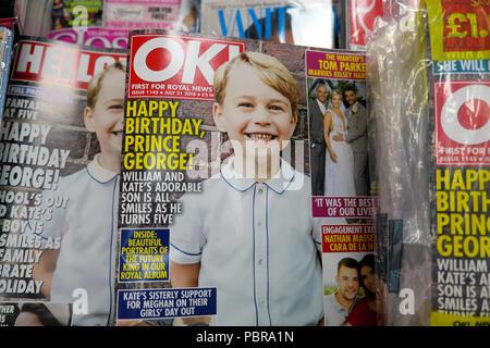 5º aniversario de Prince George sonriente en la portada de la revista OK y revistas en un quiosco en el estante de WH Smith tienda en Londres Reino Unido KATHY DEWITT