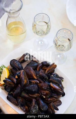 Vino blanco y mejillones en una shell en un café en la mesa