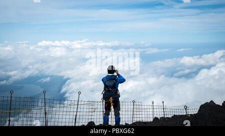 Escalador mirando por encima de las nubes desde la cumbre del Monte Fuji en Japón