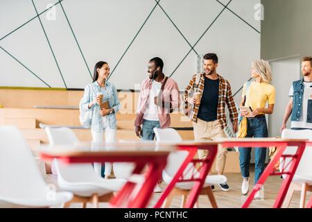 Grupo de jóvenes estudiantes pasar tiempo juntos en la sala de conferencias de la universidad