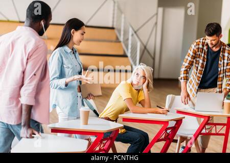 Los jóvenes estudiantes multiétnica pasar tiempo juntos en la sala de conferencias de la universidad