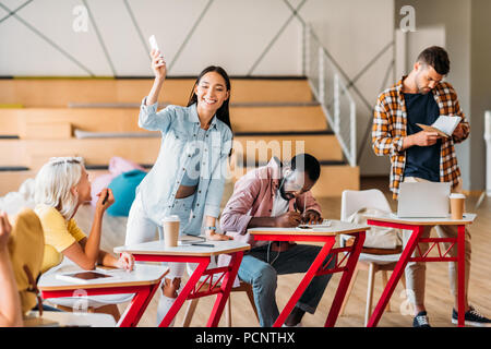 Felices los jóvenes estudiantes pasar tiempo juntos en la sala de conferencias