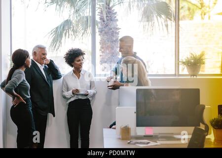 El grupo de gente de negocios tener un debate informal durante la pausa para el café. Equipo empresarial tras una pausa para el café.