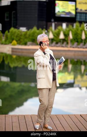 Longitud completa positivo retrato de mujer madura haciendo una llamada telefónica en el resort