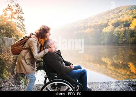 Las parejas ancianas con silla de ruedas en el otoño de la naturaleza.