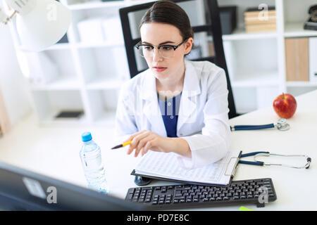 Una hermosa joven vestida con una túnica blanca está sentado frente a una computadora de escritorio con documentos y una pluma en sus manos.