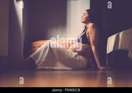 Embarazada hermosa mujer caucásica sentados en el suelo y respirar para relajarse. El nuevo concepto de la vida en el hogar