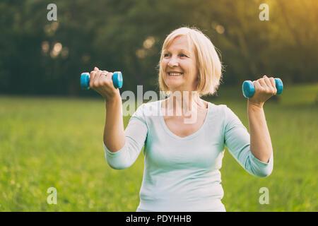 Mujer senior deportivo el ejercicio con pesas outdoor.Imagen es intencionalmente tonificado.
