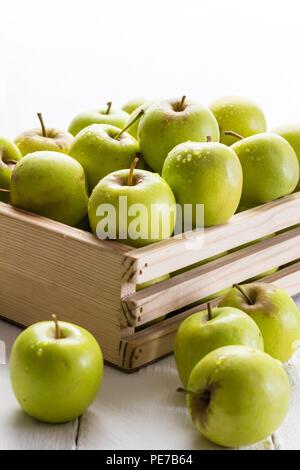 Las manzanas verdes en jaula estrecha sobre fondo blanco con el enfoque selectivo en Apple con gotas de agua
