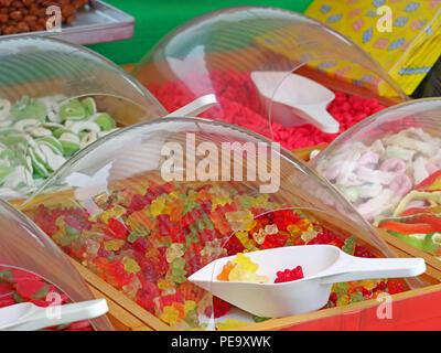 Cerca de coloridos dulces osos gomosos en mercado con cucharas de plástico blanco.