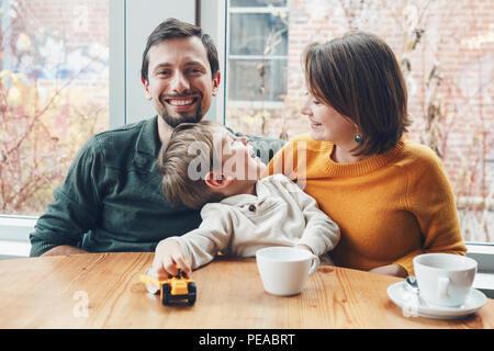 Retrato de familia feliz caucásicos blancos de tres madre, padre e hijo, sentado en el restaurante café en la mesa, sonriendo, jugando, auténtico estilo de vida Foto de stock