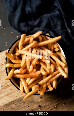 Un alto ángulo de disparo de algunas apetitosas papas fritas servidas en un cuenco de cerámica blanca, colocados sobre una mesa de madera rústica gris oscuro