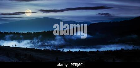 Panorama de la campiña en la noche en la luz de la luna llena. hermoso paisaje en las montañas con la niebla se eleva por encima del valle y colina Foto de stock
