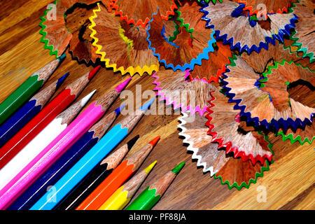 Lápices de colores y sus virutas sobre una tabla de madera.