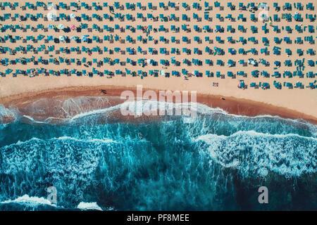 Vista superior de la antena en la playa. Paraguas, la arena y las olas del mar