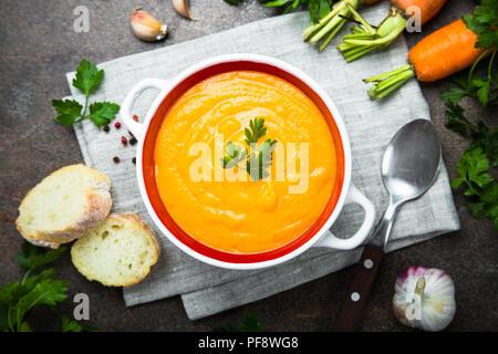 Sopa crema de calabaza zanahoria en mesa de piedra oscura. Vegetariana sopa de verduras. Vista desde arriba.