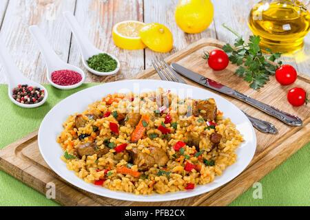 Sabrosa paella con carne, pimienta, hortalizas y especias en un plato sobre la tabla de cortar, la rodaja de limón, especias y tomates cherry sobre antecedentes, vista desde ab