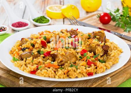 Paella con carne, pimienta, hortalizas y especias en DISH On tabla de cortar, la rodaja de limón, especias y tomates cherry sobre antecedentes, vista desde arriba, clos