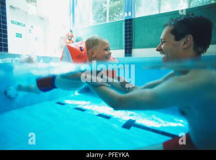 Niño usando agua alas retenidos por hombre sentado enfrente en el agua