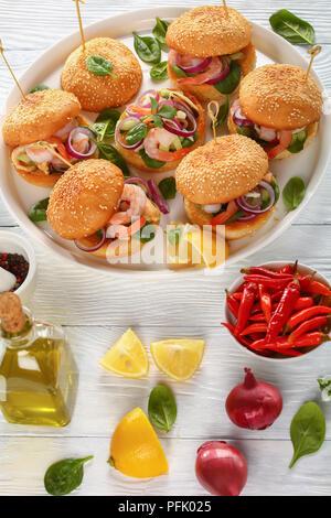 Asado jugoso burgesr anclado con pinchos o brochetas de bambú con mariscos, camarones, mejillones, calamares, tiras de cebolla roja y las espinacas en manjar blanco, España
