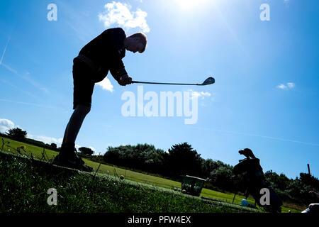 Joven adolescente tomando un swing en una pelota de golf por primera vez. Foto de stock