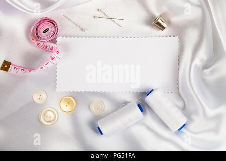 Accesorios de costura y una nota sobre tela satinada blanca. Tela satinada blanca, hilo, dedal, pasadores y cinta métrica.