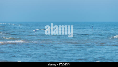 Ondas áspero en un hermoso mar azul en un verano, sol y viento del día. Banderas de advertencia que sobresale del mar.