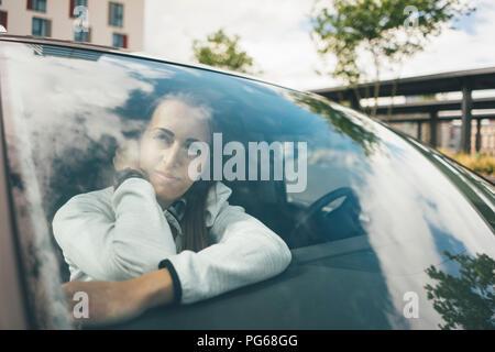 Sportive joven en coche mirando hacia afuera de la ventana