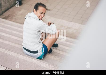 Deportivo sonriente joven sentado en las escaleras exteriores