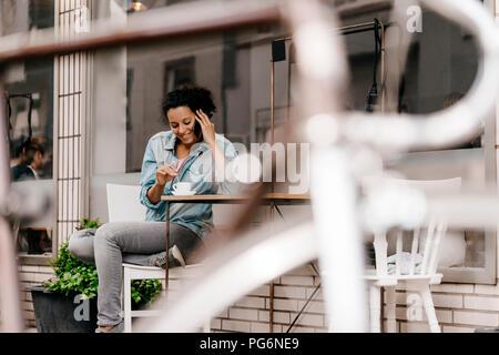 Mujer joven bebiendo café en frente de la cafetería, hablando por el teléfono