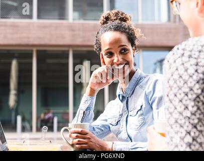 Jóvenes colegas sentados al aire libre, trabajando juntos, almorzar