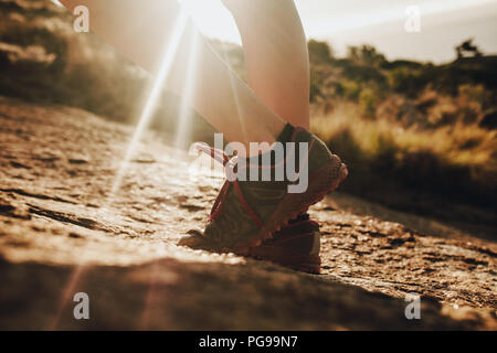 Cerrar cerro hembra trail runner llevar calzado deportivo de pie en la luz del sol. Mujer con zapatillas de pie en sendero rocoso.